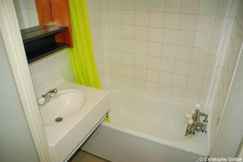 La salle de bain avec baignoire et lavabo