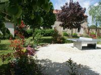 Un grand jardin avec un barbecue fixe pour profiter des extérieu