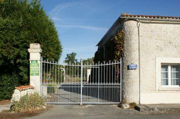 L'entrée du jardin avec un parking 3 places à gauche du gîte.