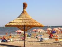 La plage avec lits et parasols