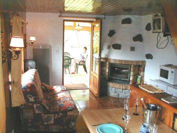Le séjour, sa cheminée, et sa sortie sur la terrasse abritée.